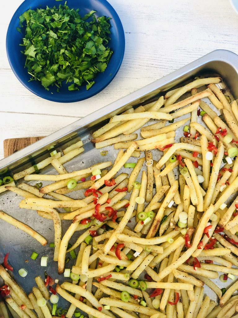 oven chips scattered with sliced spring onions, red chillies and chinese spices - saucer of chopped coriander to the side of the tray