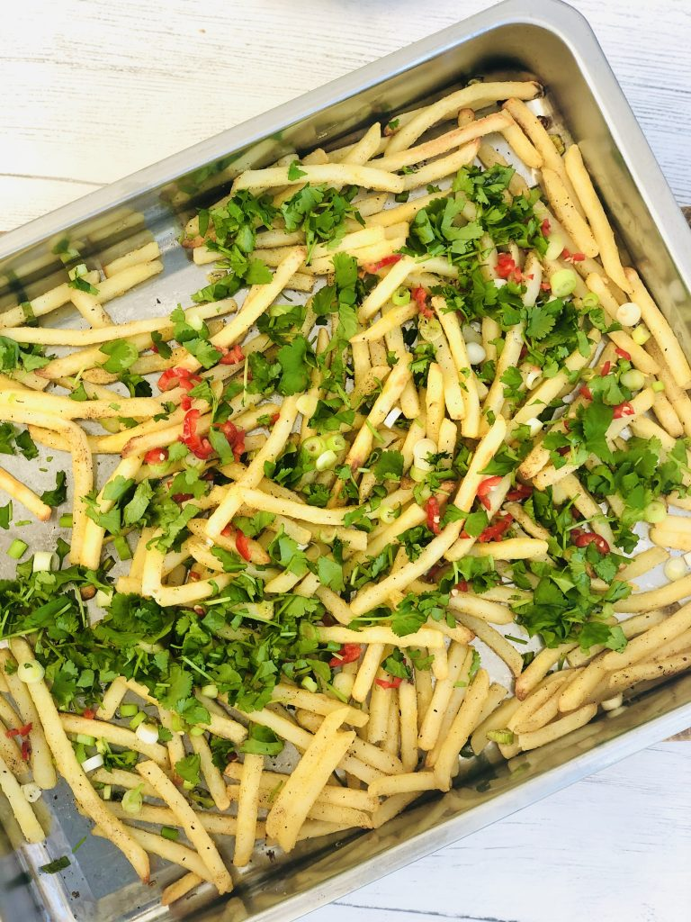 tray of freshly baked salt and pepper chinese style chips scattered with Chinese spices, sliced spring onions and red chillies and chopped coriander
