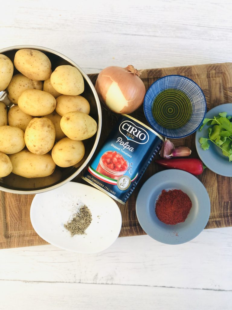 ingredients for patatas bravas - new potatoes, polpa chopped tomatoes, onion, olive oil, flat leaf parsley, smoked paprika, sea salt and black pepper, red chilli, garlic cloves