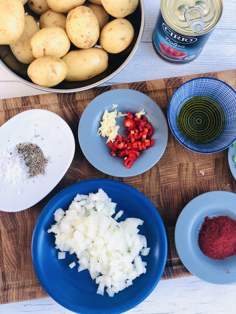 ingredients for patatas bravas - new potatoes, tin chopped tomatoes, black pepper, sea salt, chopped red chillies, grated garlic cloves, chopped onions, smoked paprika, olive oil and flat leaf parsley