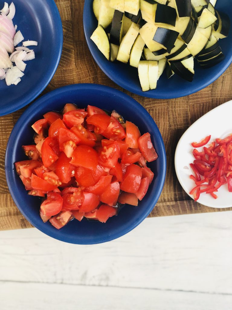 diced tomatoes, diced aubergine, sliced shallots and slice red chillies on a wooden chopping board