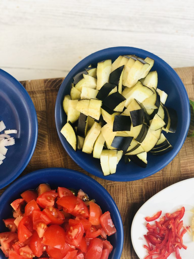 diced aubergine, diced tomatoes, sliced red chillies on a wooden chopping board
