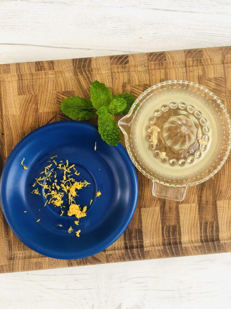 zest of a lemon, juiced lemon in a juicer alongside a bunch of mint leaves