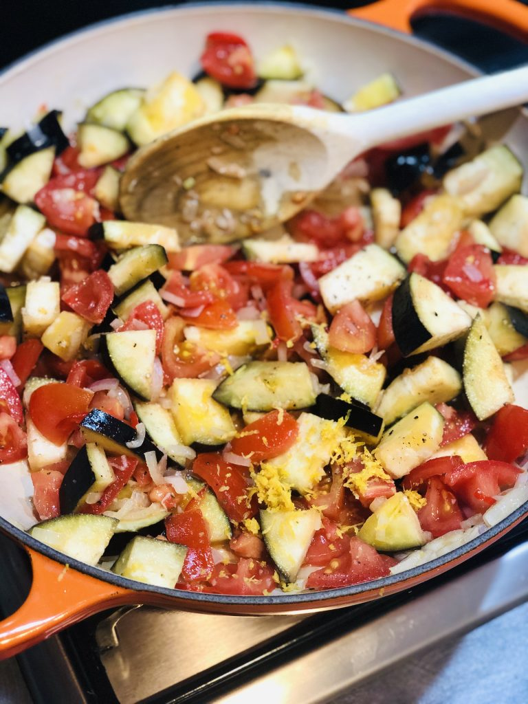 enamel skillet pan filled with aubergine, tomatoes, chillies, shallots, lemon zest being stirred with a wooden spoon