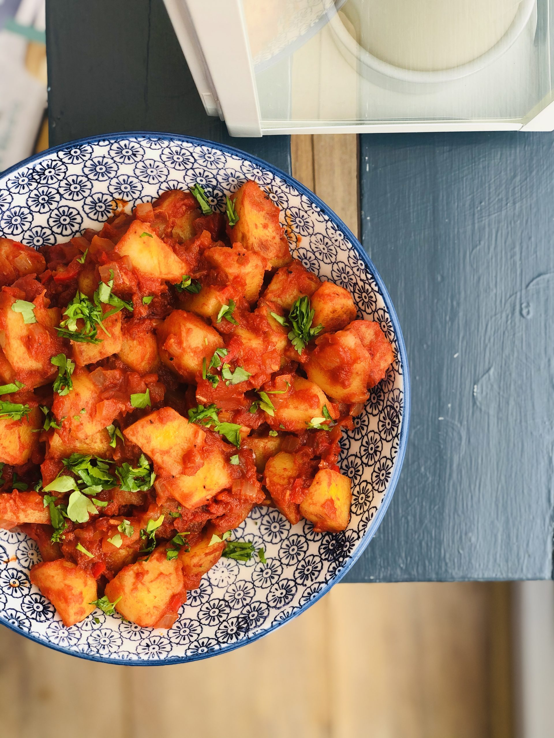 homemade patatas bravas in a blue and white bowl on a dark blue wooden table