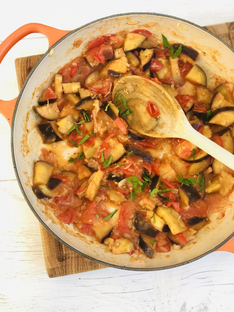 enamel skillet pan filled with homemade aubergine tapas with tomatoes, garlic, chillies and chopped herbs