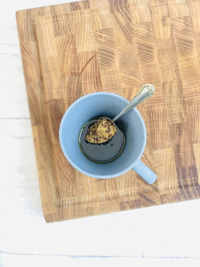 small blue coffee cup filled with olive oil, balsamic vinegar and a spoonful of Maille wholegrain mustard