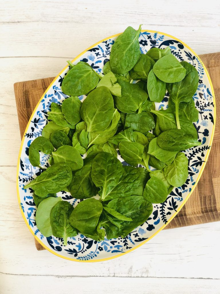large blue and yellow plate scattered with spinach leaves