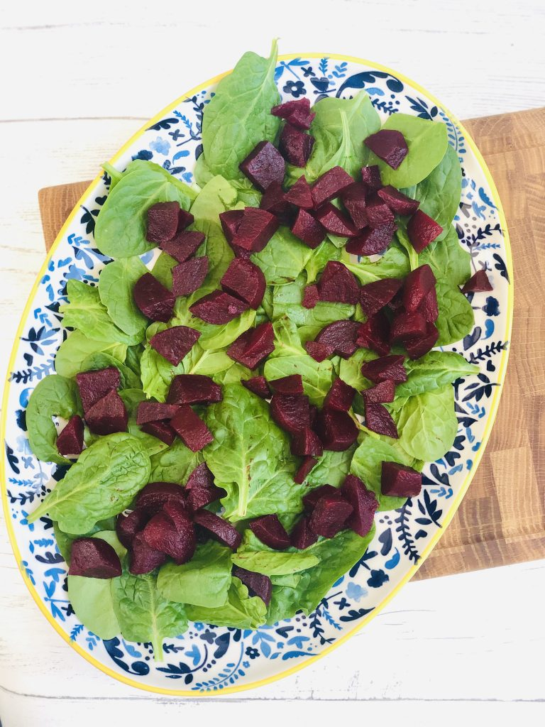 large blue and yellow plate scattered with baby spinach leaves and chopped beetroot