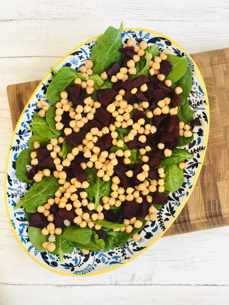 large blue and yellow plate scattered with baby leaf spinach, chopped beetroot and chickpeas