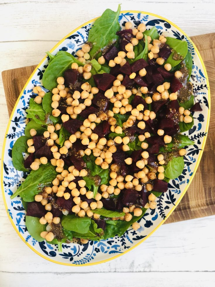 large blue and yellow plate scattered with baby spinach leaves, chopped beetroot, chickpeas and drizzled with homemade mustard and balsamic salad dressing