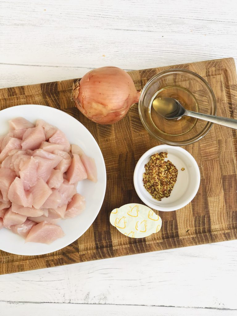 ingredients for honey and mustard chicken - diced chicken breast, onion, wholegrain mustard, chicken stock and small bowl of honey all gathered together on a wooden chopping board