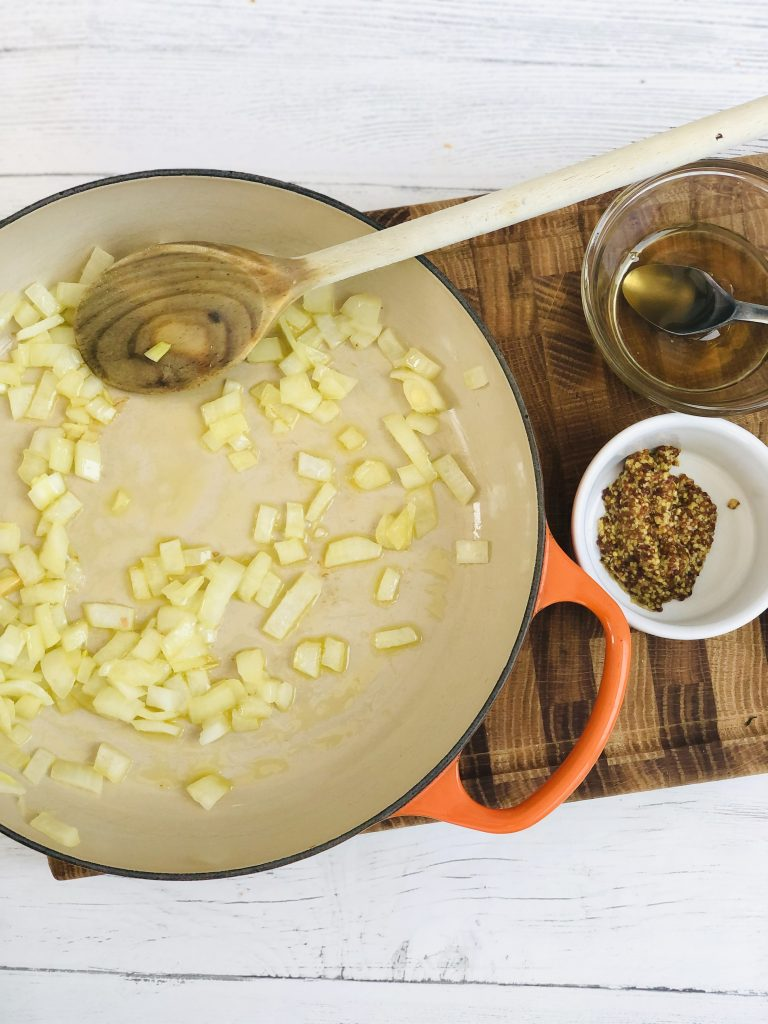 enamel skillet pan with onions being fried in olive oil, small bow of honey and mustard are next to the pan