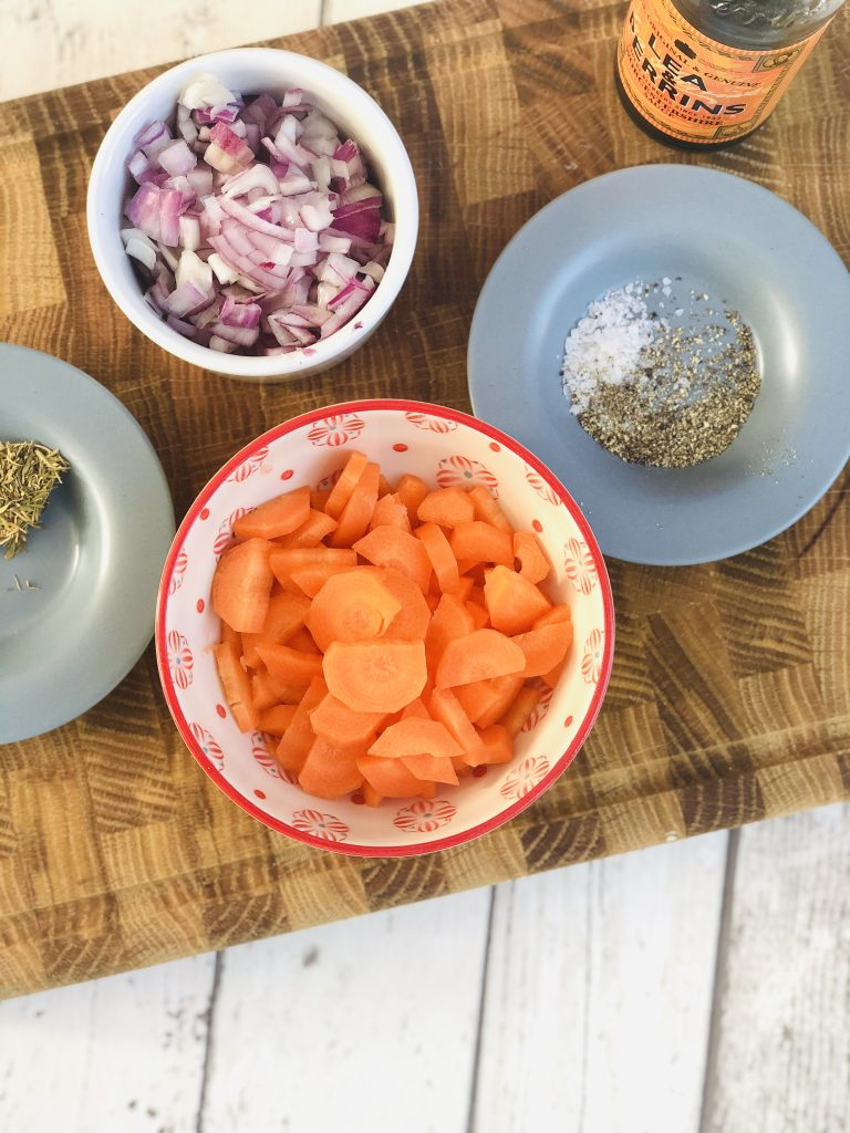 white bowl filled with finely chopped red onion, small red and white bowl filled with peeled and sliced carrots alongside two pale blue saucers one with dried thyme on and one with salt and pepper on it. Bottle of Worcestershire Sauce stood on wooden chopping board alongside