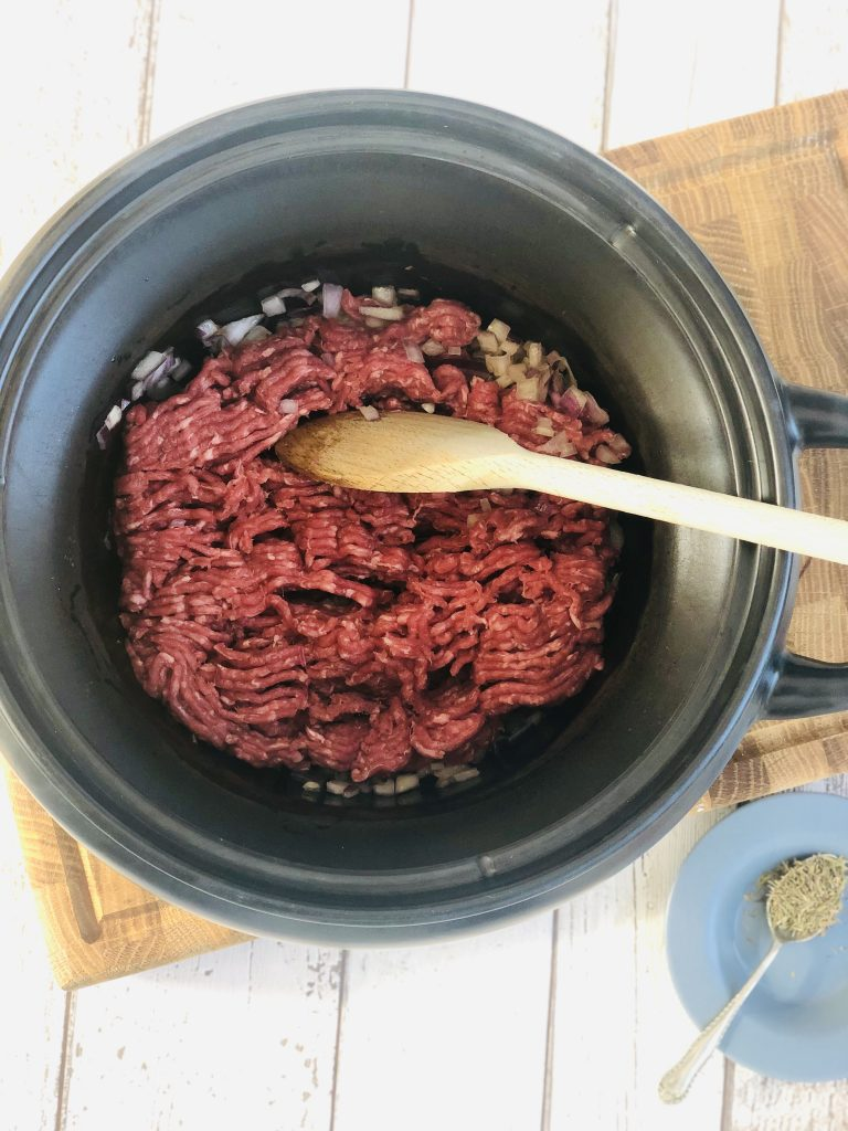 black crockpot slow cooker pan filled with sautéed red onions and a pack of beef mince just been dropped in