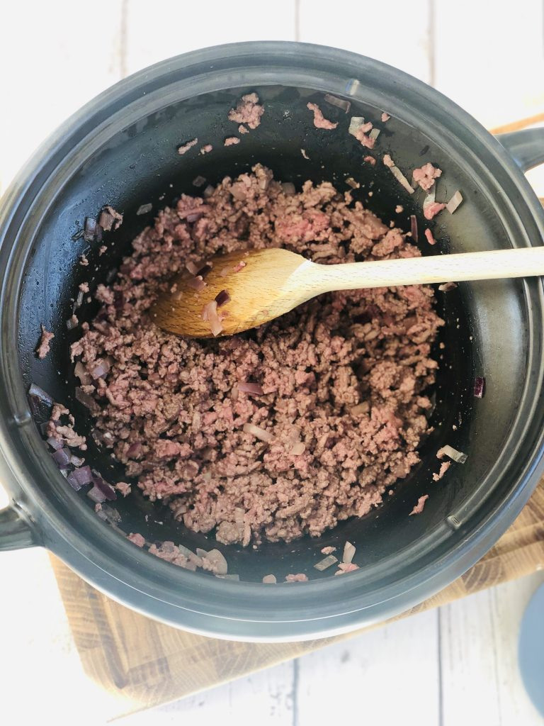 black crockpot slow cooker pan filled with sautéed red onion and browned beef mince all being stirred with a wooden spoon