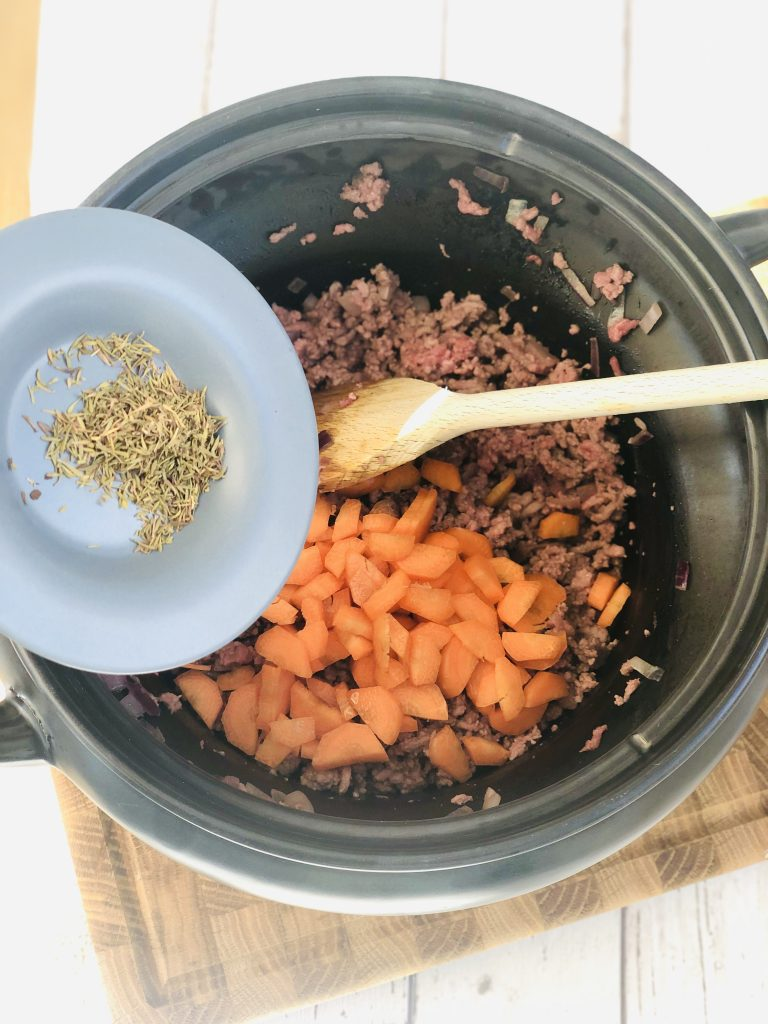 small saucer of dried thyme being tipped into a black slow cooker crockpot pan that has browned beef mince, onions and carrots in it