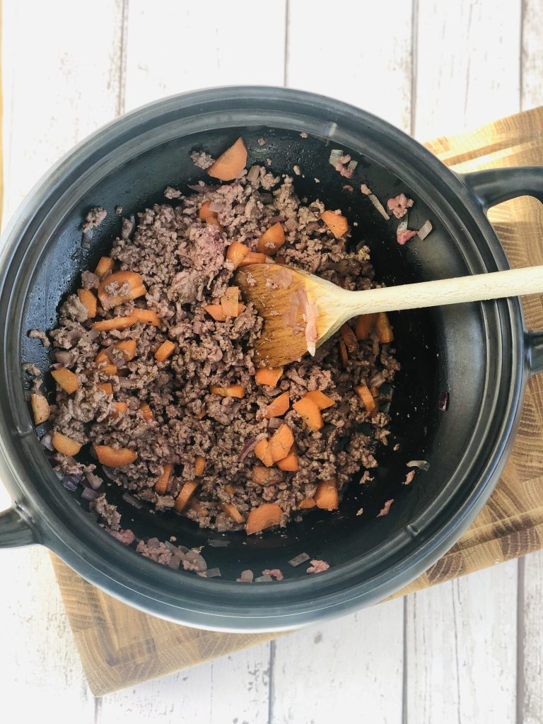 black crockpot slow cooker pan filled with browned beef mince, onions and carrots