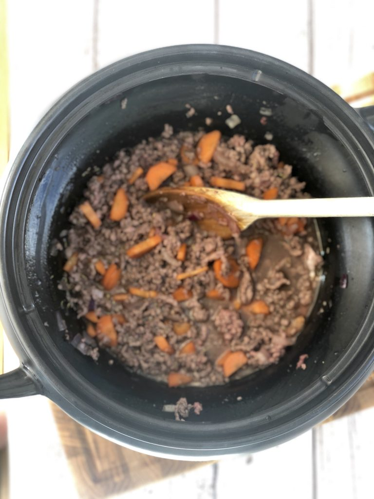 black crockpot slow cooker pan filled with browned beef mince, carrots, onions and beef stock seasoned with salt, pepper and thyme