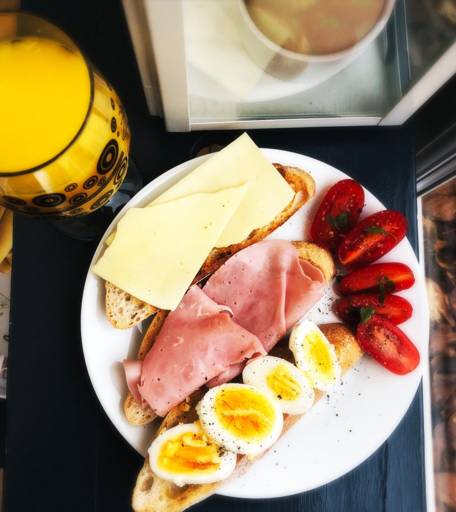 three slices of sourdough toast buttered and topped with cheese, ham and sliced egg. Baby plum tomatoes halved and scatter with sea salt flakes and black pepper. Glass or orange juice alongside