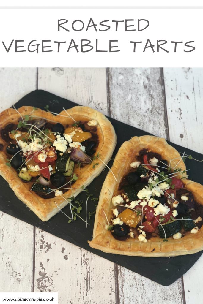 roasted vegetable tarts - heart shaped with roasted Mediterranean vegetables and feta cheese served on a black slate board