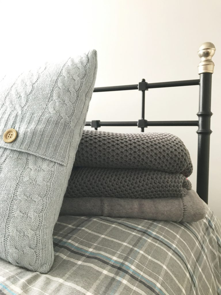 cast iron bedstead with grey checked bedding with grey woollen throw in a pile on the bed