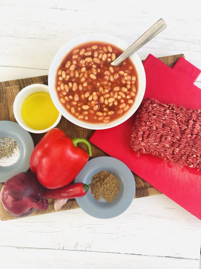 ingredients for quick chilli con carne - 500g beef mince, bowl of BBQ baked beans, white bowl with olive oil, red pepper, red onion, red chilli, two cloves garlic, small blue saucer with ground cumin, small blue saucer with sea salt and black pepper on a wooden chopping board