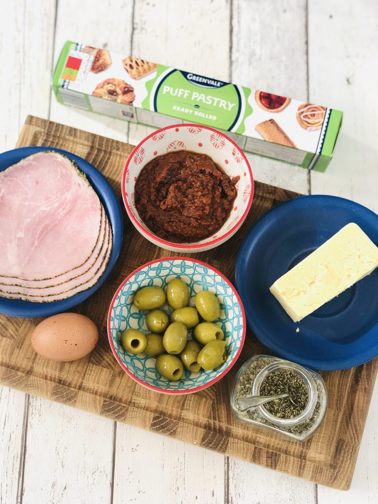 ingredients to make puff pastry pizza - packet of ready rolled puff pastry, four slices of ham, bowl of sun dried tomato pesto, bowl of green olives, block of mature cheddar cheese, little jar of dried oregano, egg