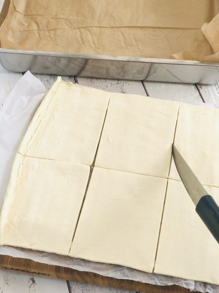 ready rolled puff pastry sheet being cut with a joseph joseph knife into 8 equal pieces