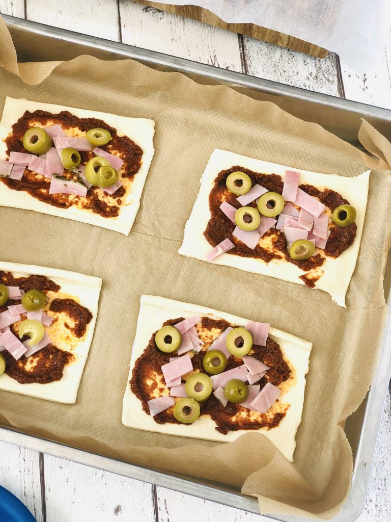 four puff pastry triangles topped with sun dried tomatoes, chopped ham and sliced olives - mini puff pastry pizzas are on baking paper on a baking tray