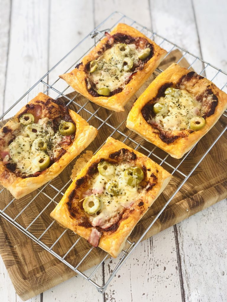 four homemade puff pastry pizzas topped with tomato pesto, ham, cheese and olives cooling on a cooling rack