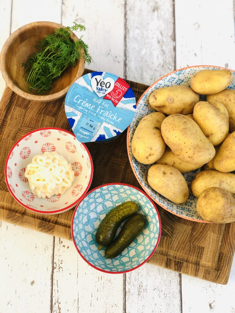 ingredients for Swedish potato salad - new potatoes in a bowl, small bowl with 2 gherkins in it, bowl of mayonnaise, pack of Yeo Valley creme fraiche, wooden bowl with a large bunch of dill