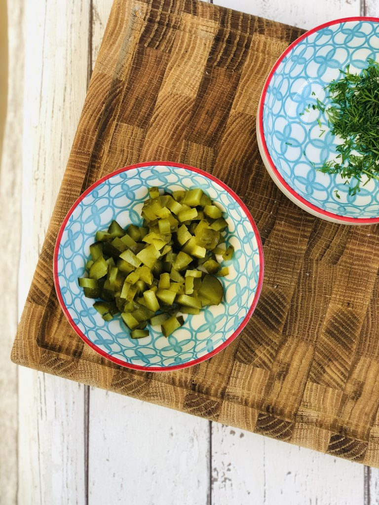 small blue and white bowl filled with finely diced gherkins, bowl of chopped dill in background