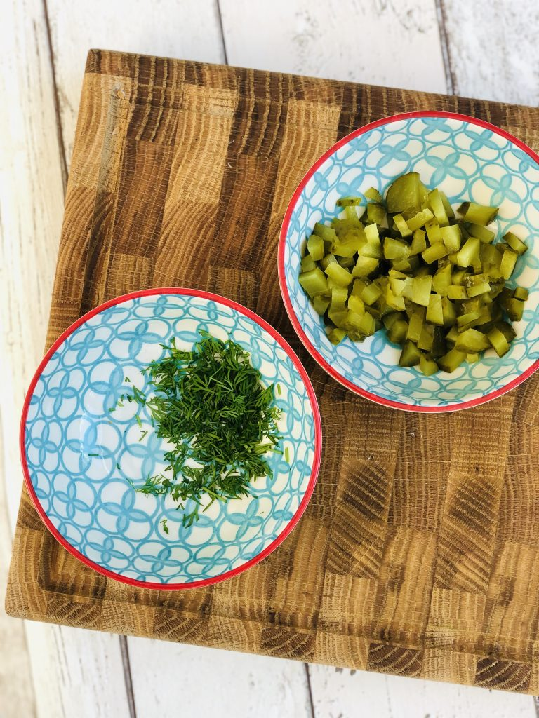 small blue and white bowl filled with chopped dill - bowl of chopped gherkins in the background