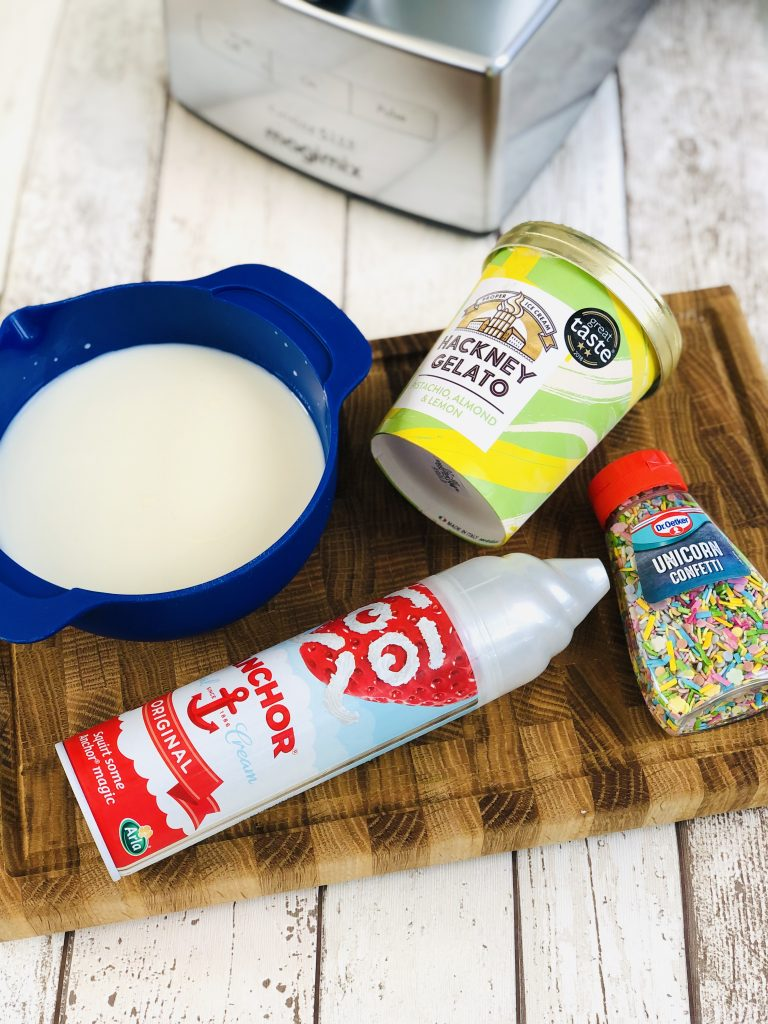 ingredients for pistachio ice cream milkshake - 300ml full fat milk, tub of pistachio and almond ice cream, can of squirty cream and pot of unicorn sprinkles all together on a wooden board