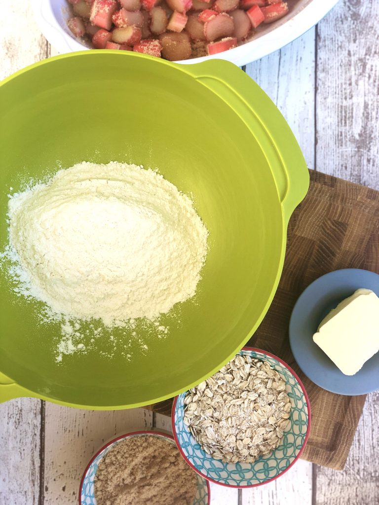 green joseph joseph mixing bowl filled with plain flour, bowl of oats, bowl of sugar and block of butter alongside with the mixing bowl