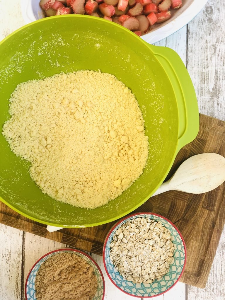 green josesph joseph mixing bowl filled with plain flour with butter rubbed into it - small bowls with sugar and oats next to the mixing bowl