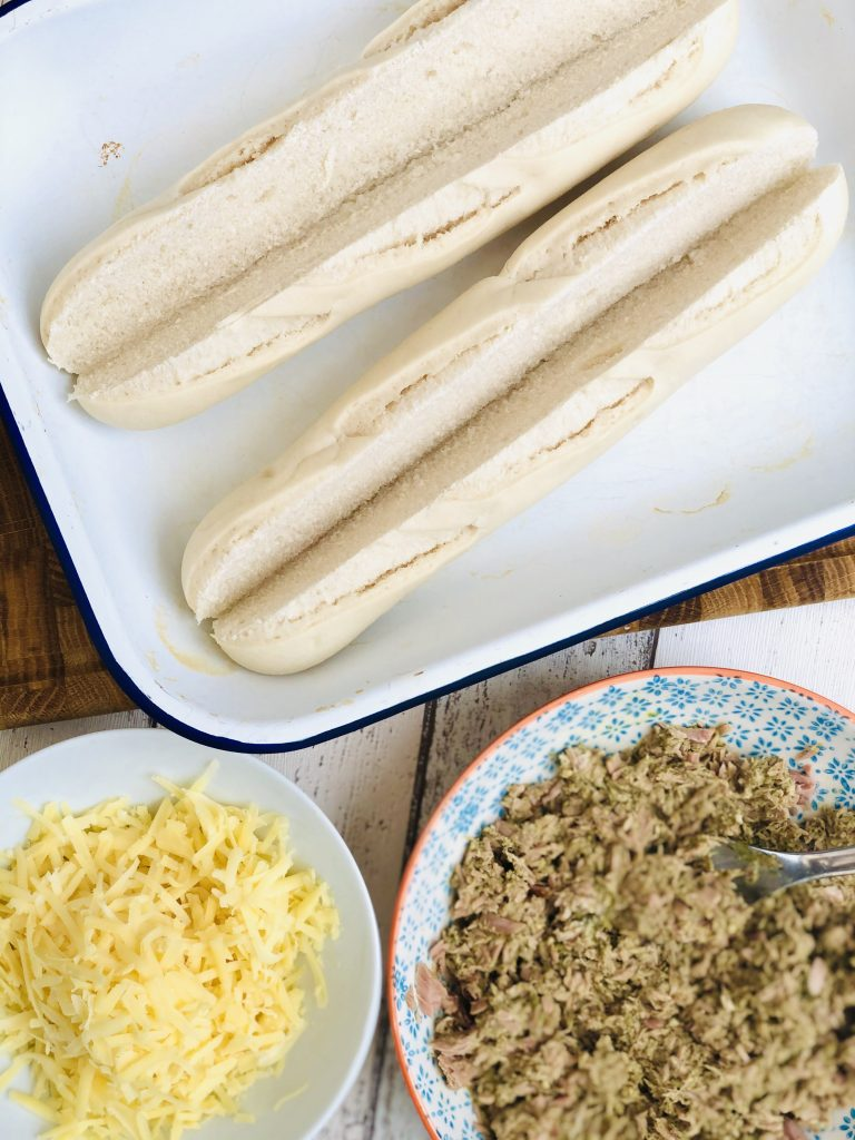 two part baked baguettes split down the middle, bowl of pesto tuna sandwich filler and grated cheese by the side of the baguettes ready to fill them