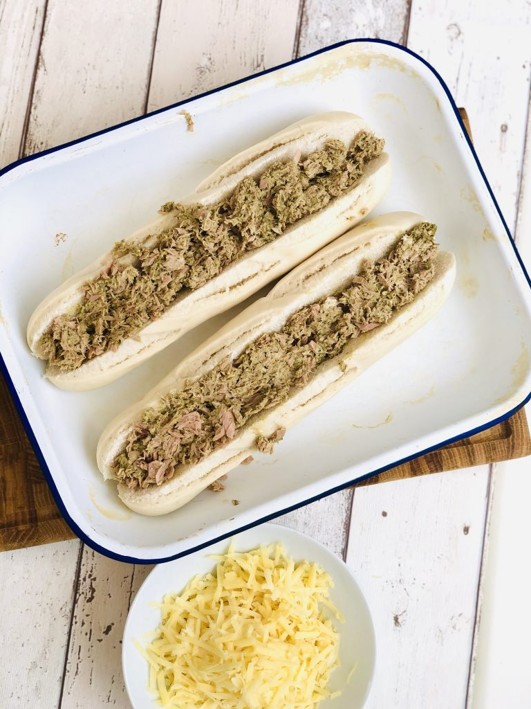 enamel baking tray with part baked baguettes split down the middle and stuffed with homemade creamy pesto tuna sandwich filling, bowl of grated cheese waiting by the side to be sprinkled on top of the tuna.