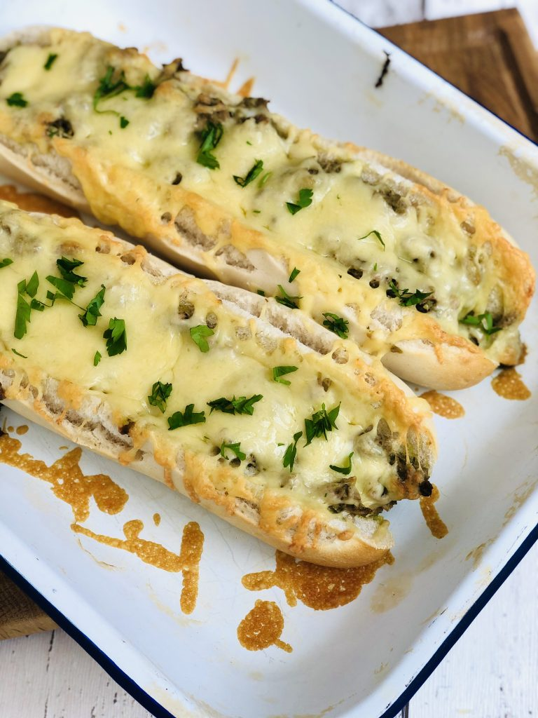 freshly baked tuna cheese melt baguettes with delicious melted cheese dripping from the sides of the baguette. Top of the tuna melts has been sprinkled with chopped flat leaf parsley. Baguettes are on an enamel baking tray on a wooden chopping board