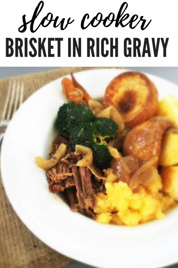 "slow cooker brisket and gravy served with mashed swedes, yorkshire pudding, roast potatoes, broccoli and loads of gravy. text overlay ""slow cooker brisket in rich gravy"""