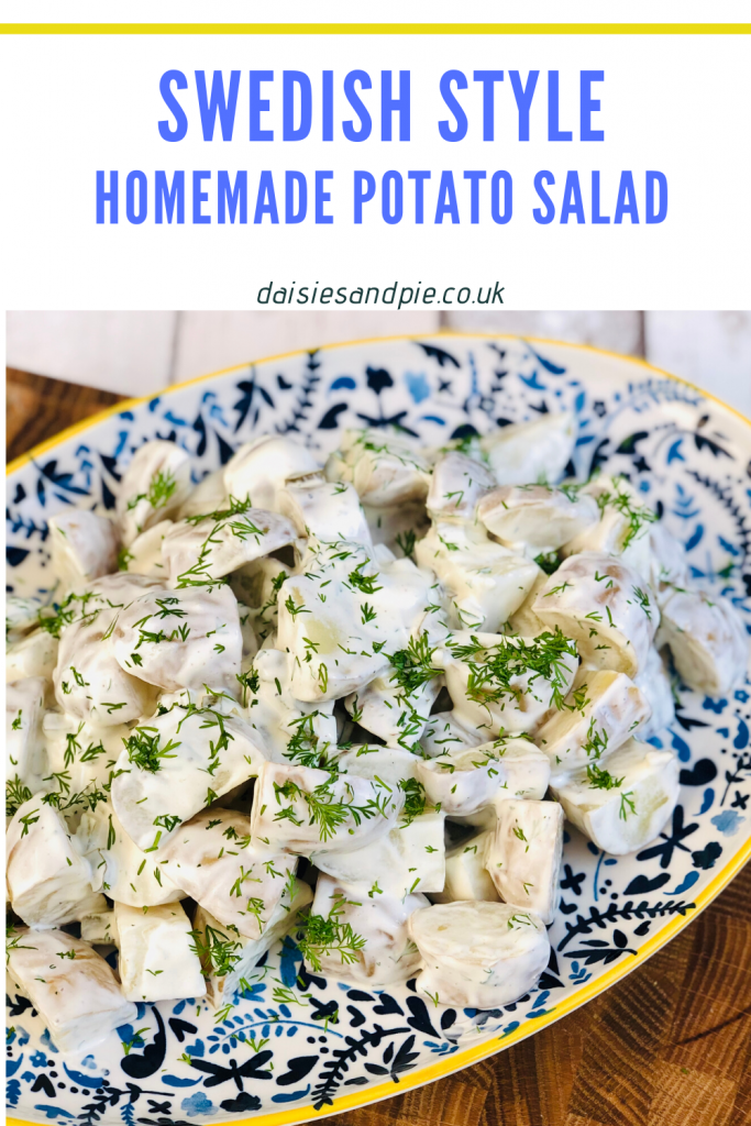 homemade Swedish style potato salad scattered with chopped dill on a blue, white and yellow floral platter