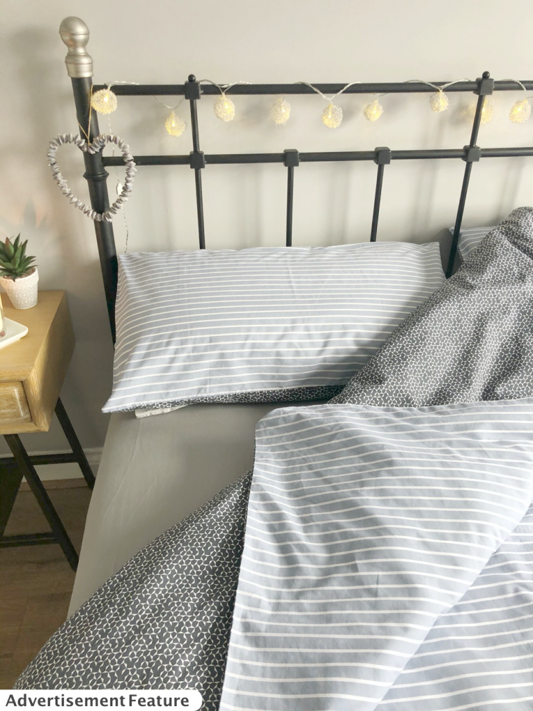 black iron bedstead with he bed made up with Silentnight blue grey striped bedding with contrasting dark grey navy floral print on reverse. Wooden Loaf bedside table by the bed with Diptyque mimosa candle and small plant. Bedstead has wire balls fairy lights and a heart made from blue shells