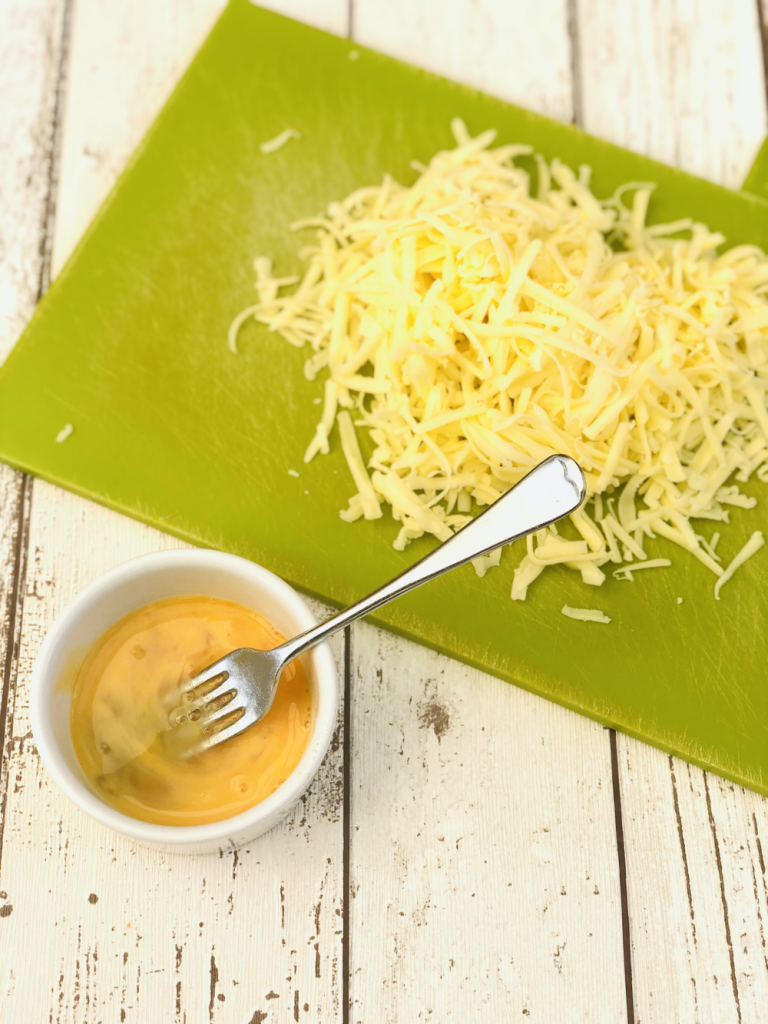 pile of grated cheddar cheese on a green Joesph Joesph chopping board with a small white bowl filled with beaten egg next to it