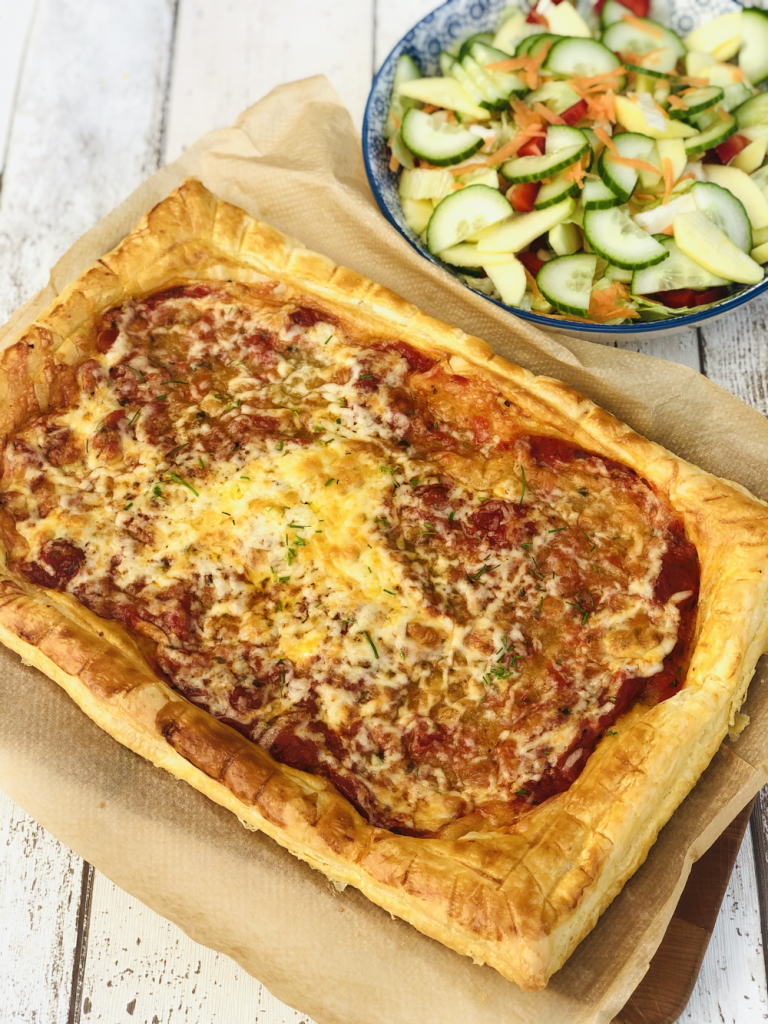 cheese and tomato tart made with puff pastry served on brown paper with a bowl of mixed salad next to it