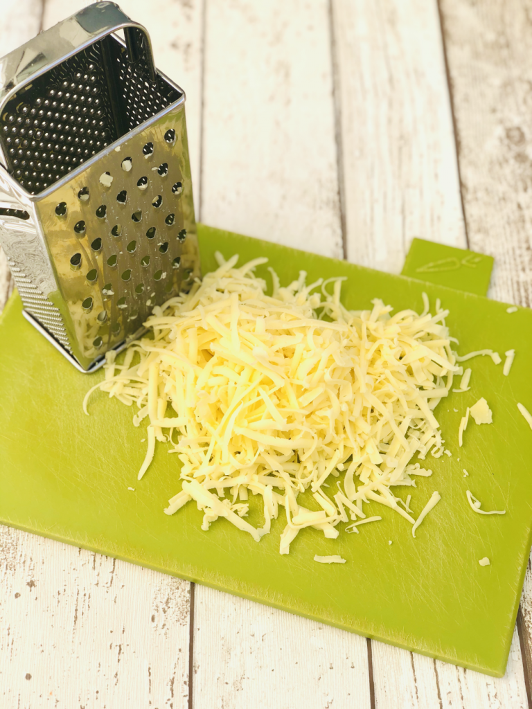 pile of grated cheddar cheese on a green Joesph Joseph chopping board with a cheese grater next to it