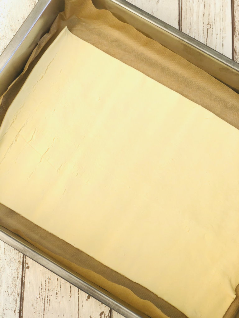 sheet of jus rol puff pastry on baking paper in a stainless steel oven tray