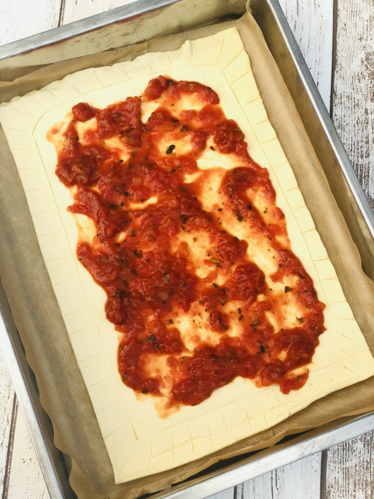 puff pastry sheet with edging scored and centre covered with spread out tomato and basil sauce