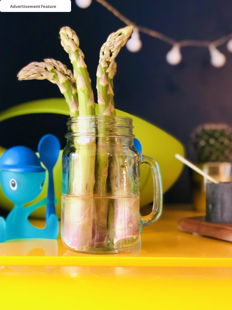 kilner jar filled with water with asparagus stood in it on top of a yellow smeg fridge.