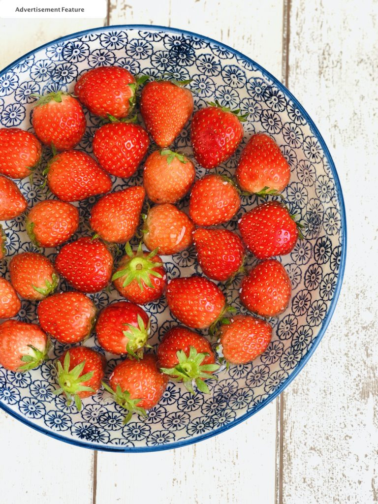 fresh strawberries being washed in water and vinegar